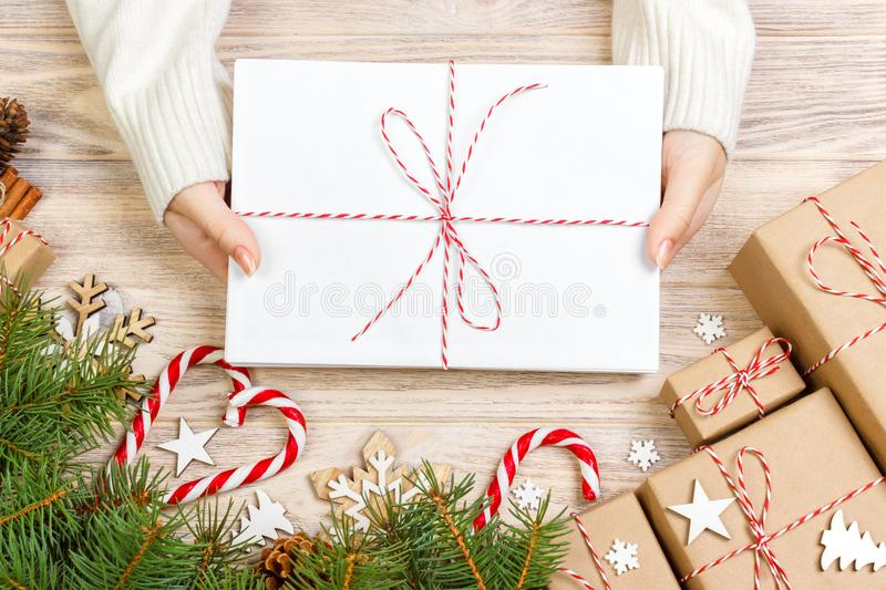 Top view of christmas letter in hand. Close up of hands holding empty wishlist on wooden table with xmas decoration royalty free stock photography