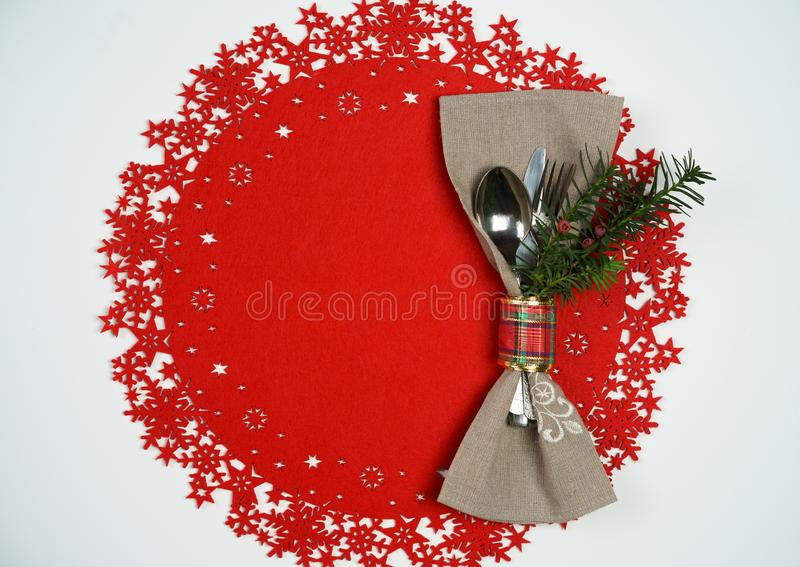 Christmas And New Year Holiday Table Place Setting with branch of Christmas tree. Top view, red woolen and white background. Top view Christmas And New Year royalty free stock image