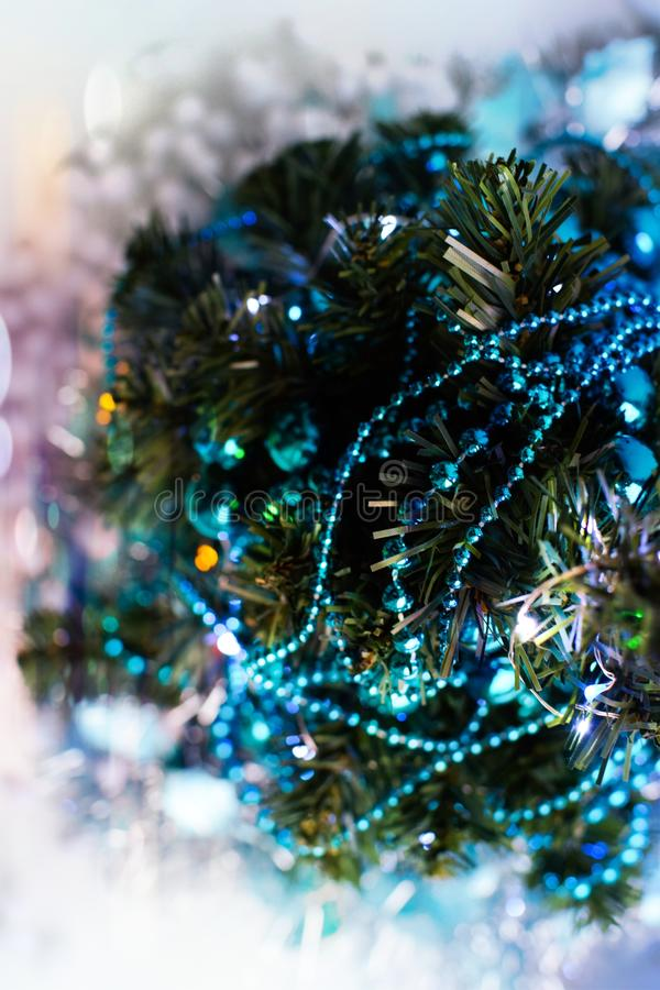 Top view of the Christmas tree, decorated with turquoise garlands, tinsel, glowing lights and artificial snow stock photos