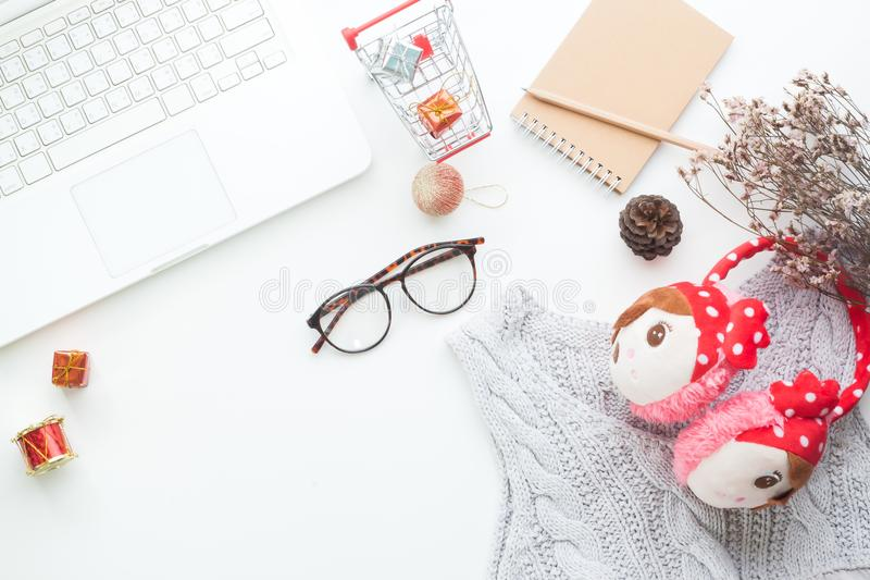 Top view of Christmas and winter shopping online concept on white desk. White laptop, shopping cart, gift boxes, notebook, eyeglas. Ses and woman accessories stock photos