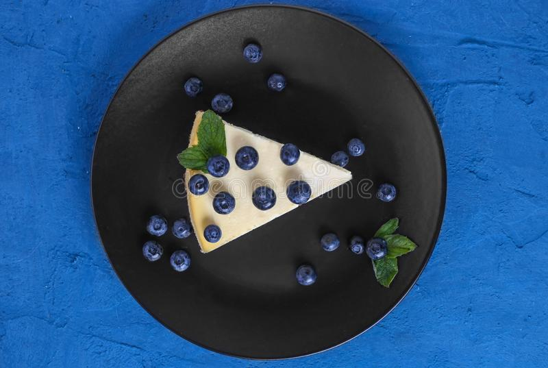 Top view classic cheesecake with blueberries and mint on a black plate. Stone blue background royalty free stock images