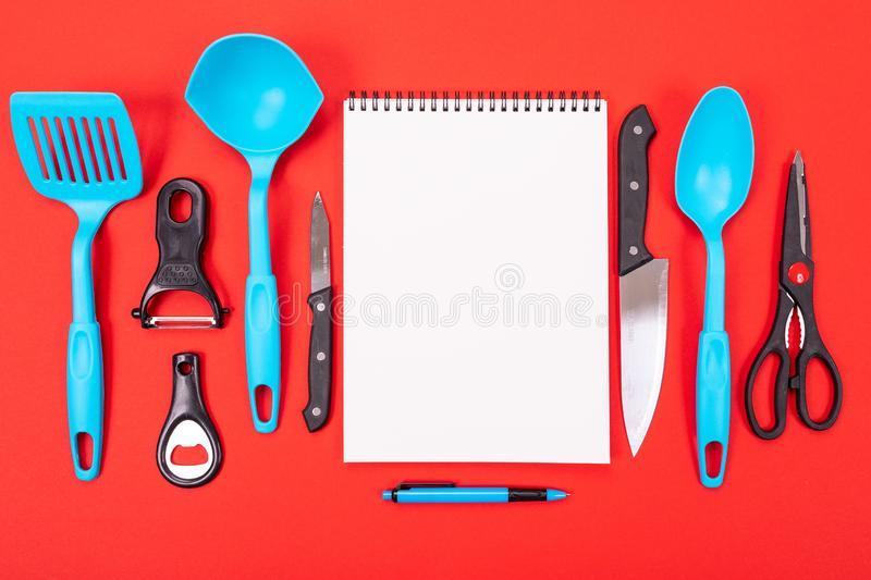 Top view of a clean sheet and kitchen utensils next to it isolated on a red background. Modern kitchen tools and a clean white sheet between them isolated on a royalty free stock photos
