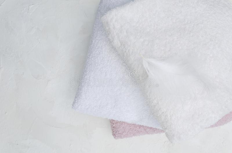 Top view of clean towels ad feather on it.Concept of soft and fluffy fabric. Laundry powder, clean towels on the white surface.Natural ligth, shadows.Empty space royalty free stock image