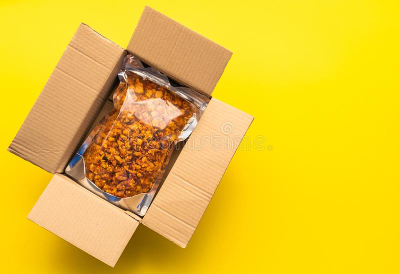 Top view clear of food bag in the brown post box on yellow paper background. Online order and delivery concept royalty free stock images