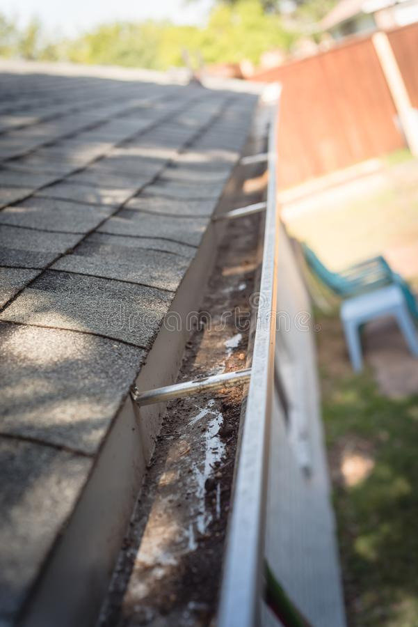 Top view clear gutter after cleaning from leaves and dirt. Clean gutter after clearing of dried leaves and dirty royalty free stock photo