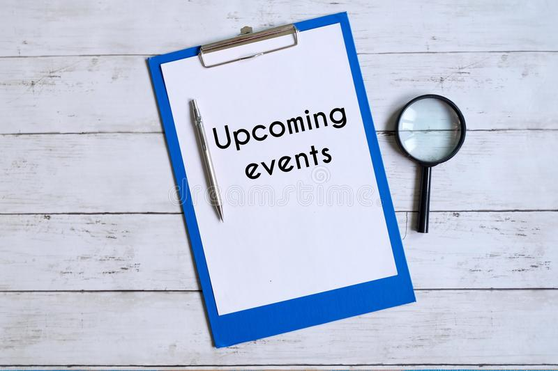 Top view of clipboard with with white paper written with `UPCOMING EVENTS` with pen and magnifying glass on white wooden backgro stock photos