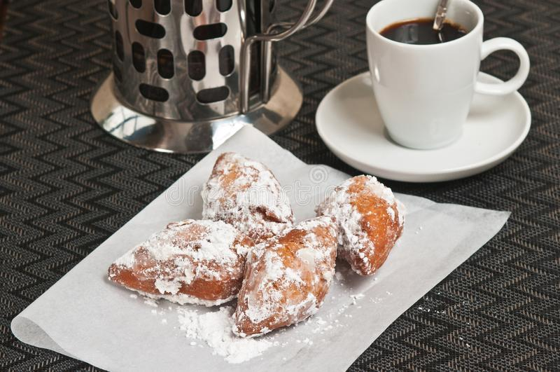 Four homemade, freshly baked beignet fritters on white napkin. Top view, close distance of four homemade, freshly baked beignet fritters covered with powdered stock photography