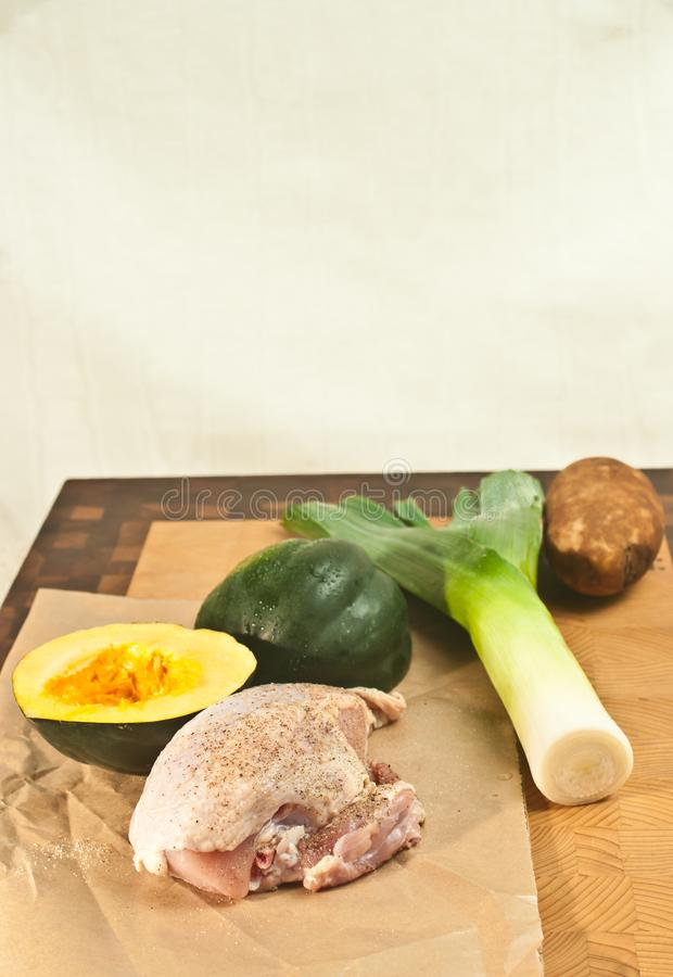 Salted and peppered raw, organic, chicken breast, washed leek, and potato, and split acorn squash, on a bamboo wood cutting board,. Top view, close medium royalty free stock image
