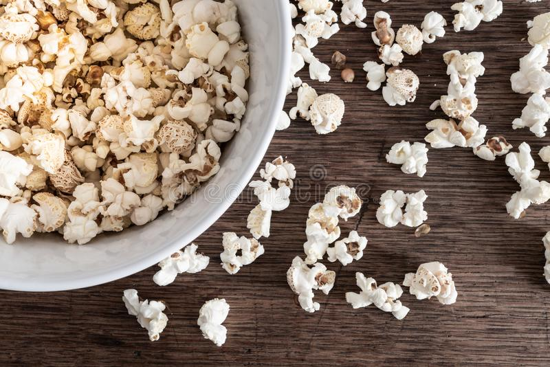 Directly above close-up of bowl filled with popcorn on rustic wooden table stock photo