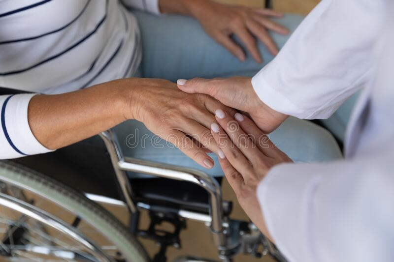 Top view close up caregiver holding disabled older woman hand royalty free stock photography