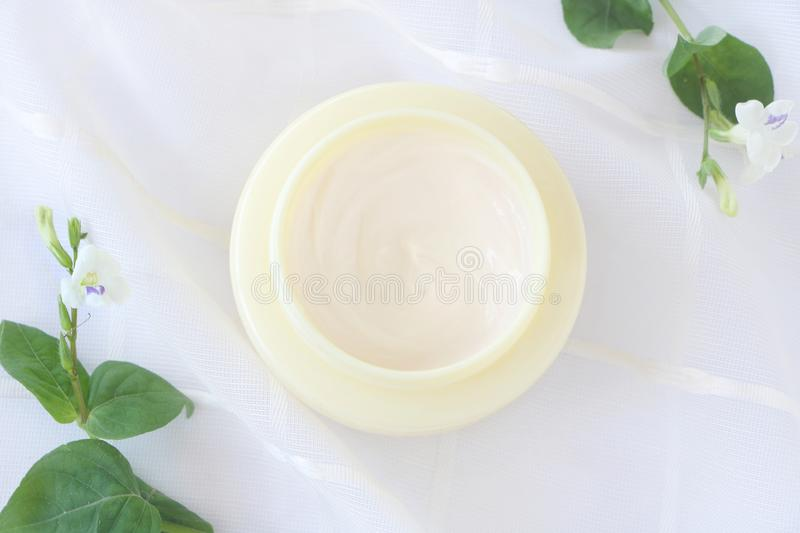 Top view of close up  cream in yellow jar on white fabric background. royalty free stock photos