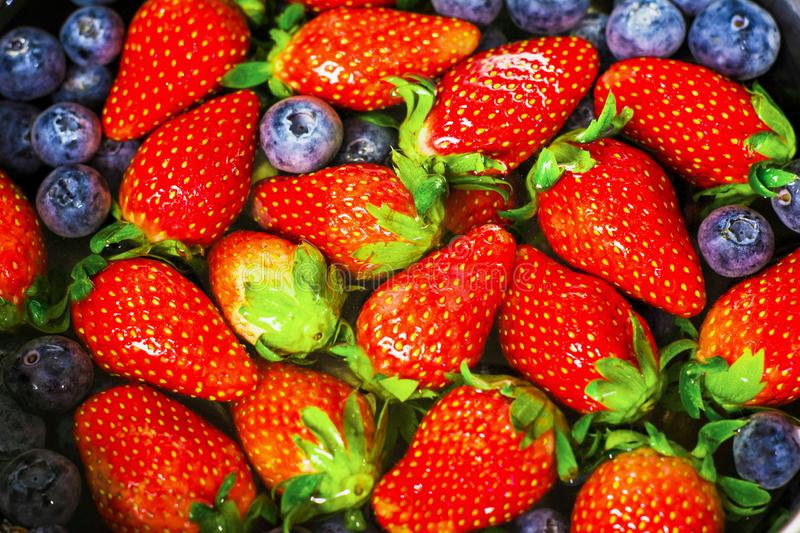 Top view- close up fresh strawberries and blueberries background, organic fruit concept with high vitamins that are beneficial to royalty free stock images