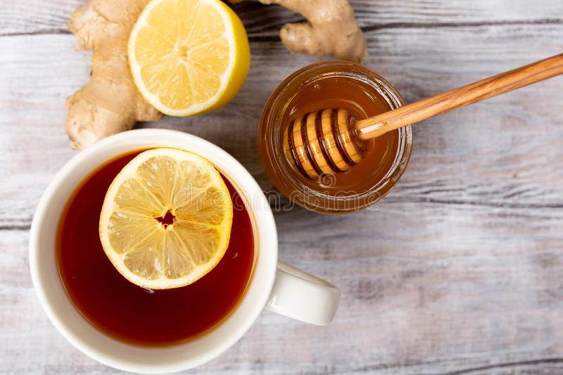 Top view. Close up. Healthy concept. Tea, lemon, ginger, honey on a white wooden background. Flat lay. Treatment of cold. Top view. Healthy concept. Tea, lemon stock photo
