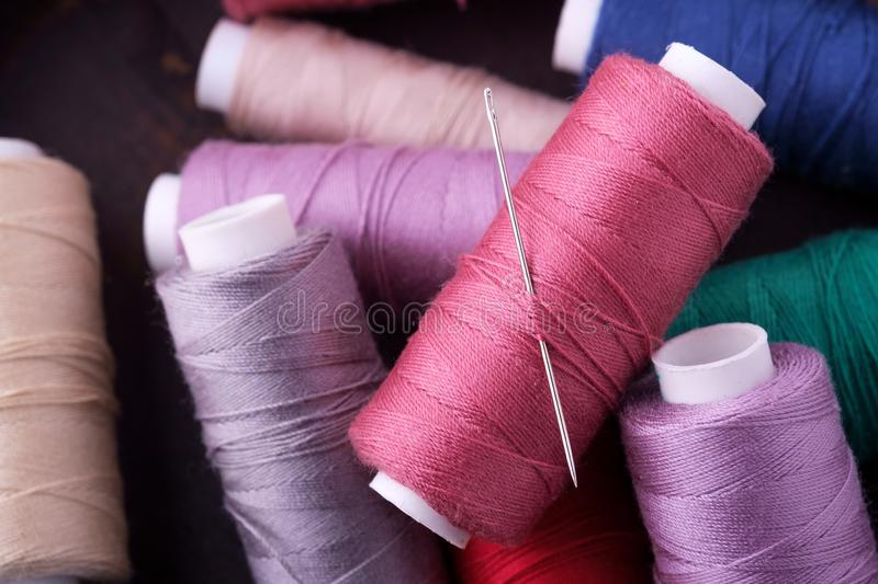 Top view close up of scattered colorful cotton thread coils with needle stock photos