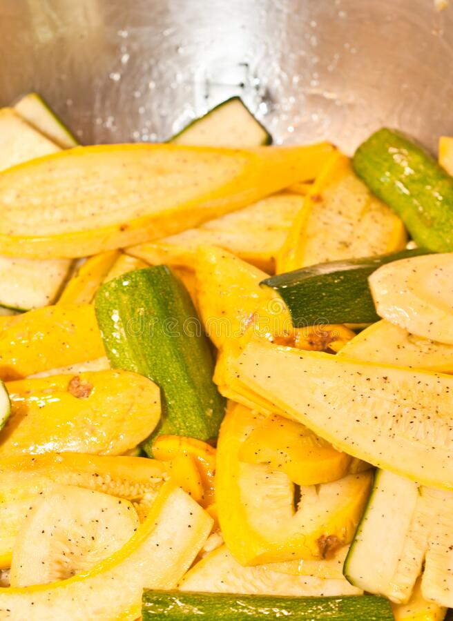 Sliced yellow and green squash with olive oil. Top view, close up of sliced yellow and green squash with olive oil, and pepper in a metal bowel royalty free stock photo