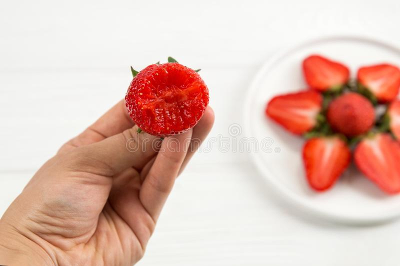 Top view. Close up. Someone holds a bitten strawberry. On a white table is a plate with lined sliced strawberries stock photography