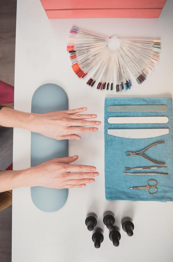 Female hands situating on desk. Top view close-up woman hands locating on table with different tools. She waiting for nail technician. Manicure in beauty salon stock images