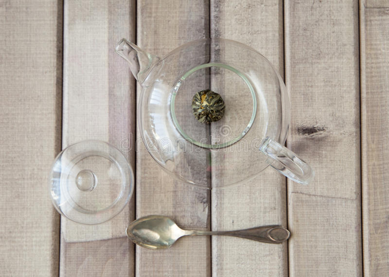 Top view closeup of a glass tea pot with Flower Chinese tea ready for brewed and a cap on wooden background in front of stock photos