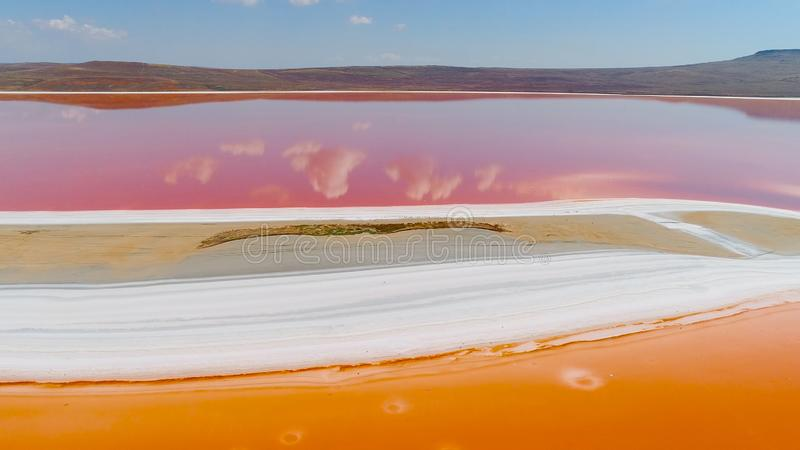 Top view of clouds reflected in pink lake. Shot. Bright colorful orange and pink lakes are separated by white shore royalty free stock photos