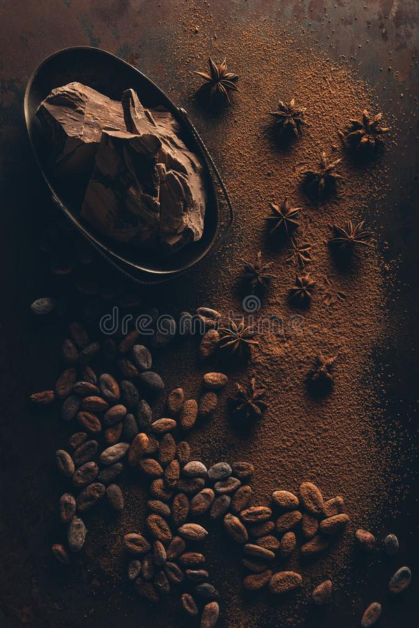 Top view of cocoa beans, star anise, chocolate pieces and cocoa powder. On dark surface royalty free stock images