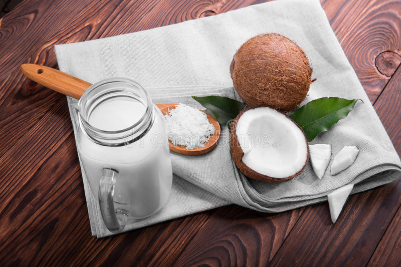 A top view on coconuts and a mason jar with milk on a wooden background. A cracked coconut and a spoon of coco chips on a sack. stock image