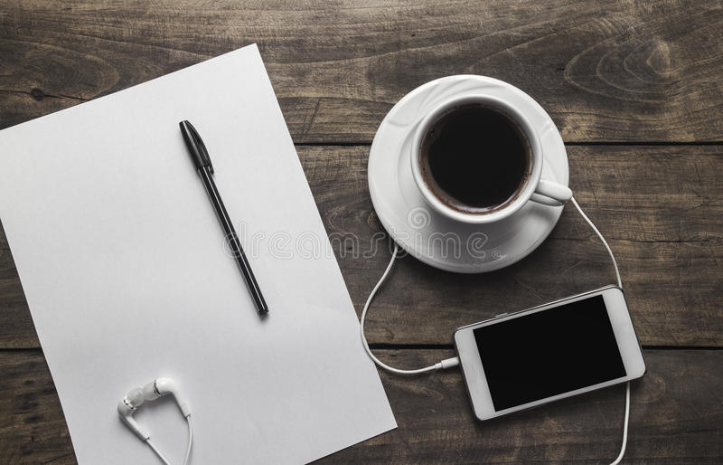 Top view of coffe ,notepad with pen and phone. On wooden table royalty free stock photo