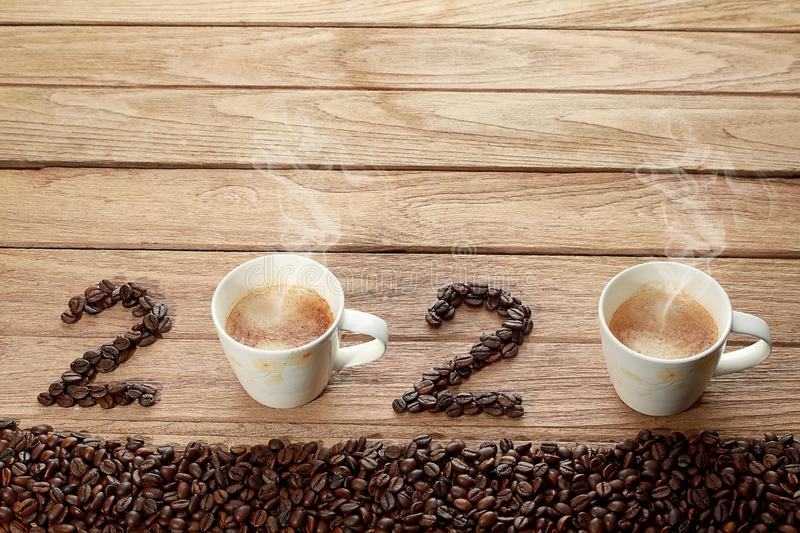 Top view of coffee beans and hot fresh coffee in a white cup with foam and smoke with text 2020 Happy New Year Concept. on wooden royalty free stock photos