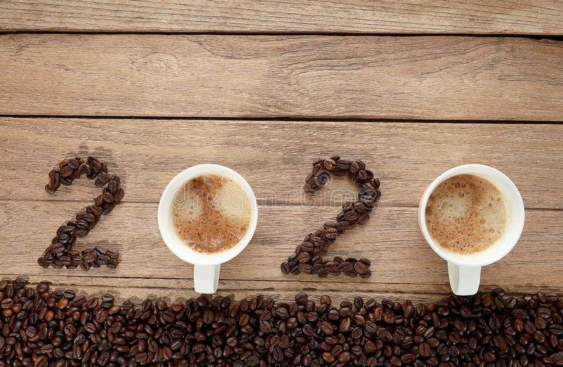 Top view of coffee beans and hot fresh coffee in a white cup with foam and text 2020 for Happy New Year Concept. on wooden table. Background royalty free stock images