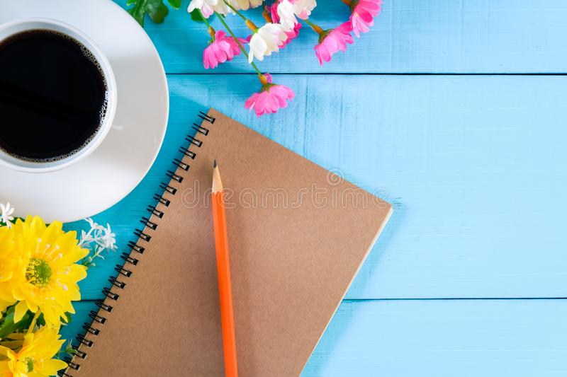 Good morning notebook and coffee. Top view coffee cup and notebook on blue wooden table nature background the good morning .decorate flower royalty free stock image