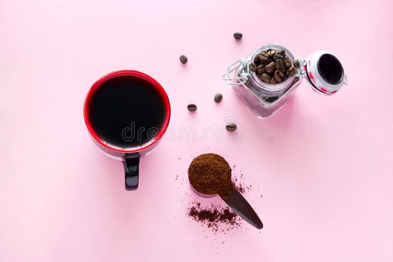 Coffee cup, spoon of ground coffee beans and jar with coffee beans on a pink background. Top view  coffee cup,  spoon of ground coffee beans and jar with  coffee royalty free stock photos