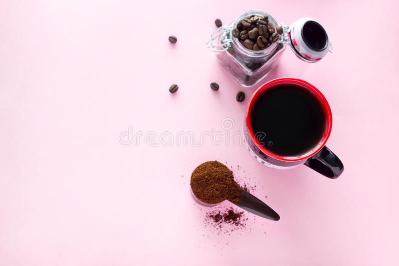Coffee cup, spoon of ground coffee beans and jar with coffee beans on a pink background. Top view  coffee cup,  spoon of ground coffee beans and jar with  coffee royalty free stock photo