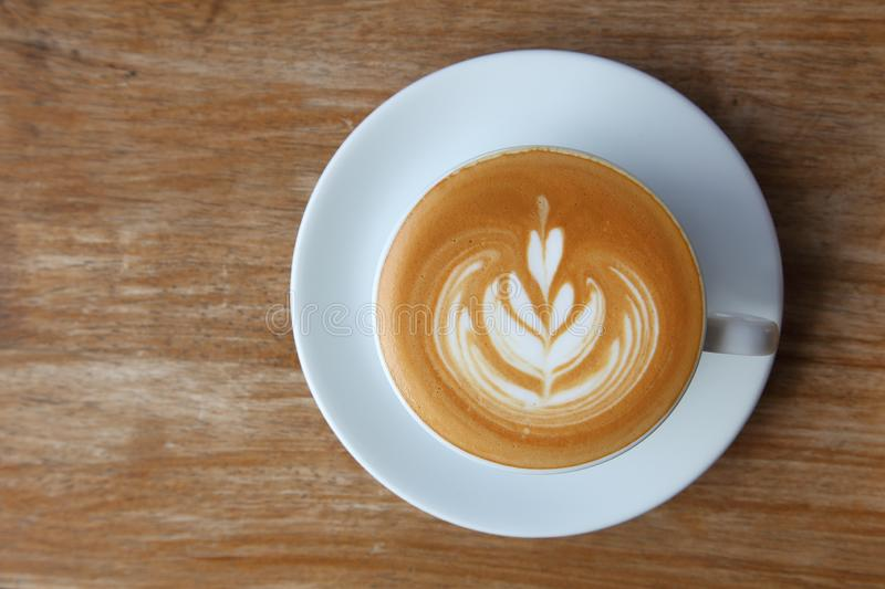 Top view of coffee latte art with tulip pattern on top on rustic wooden table bar royalty free stock image