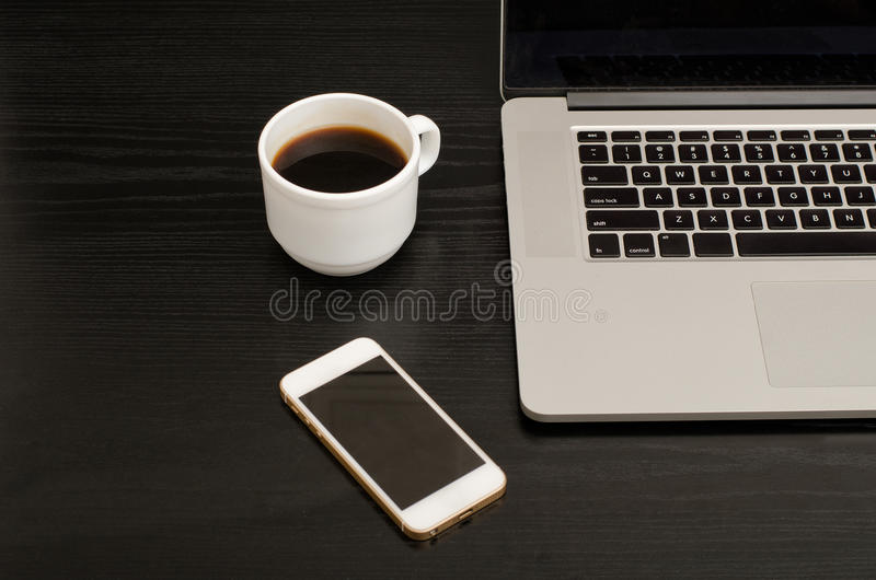 Top view of coffee mug, smartphone and laptop keyboard, black table.  stock photos
