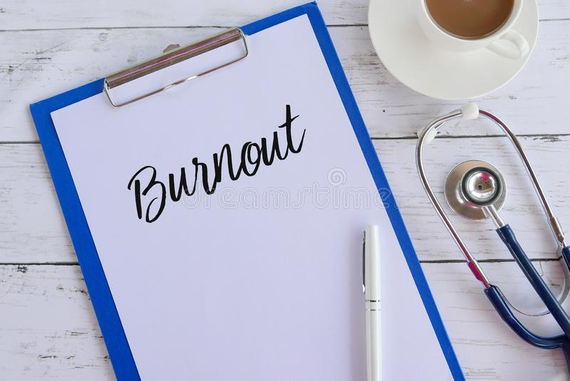 Top view of coffee,stethoscope,pen,clipboard and paper written with Burnout. Healthcare and medical concept. Top view of coffee,stethoscope,pen,clipboard and royalty free stock images