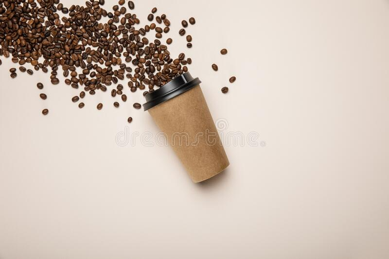 View of coffee to go and. Top view of coffee to go and scattered fresh coffee beans on beige background stock image