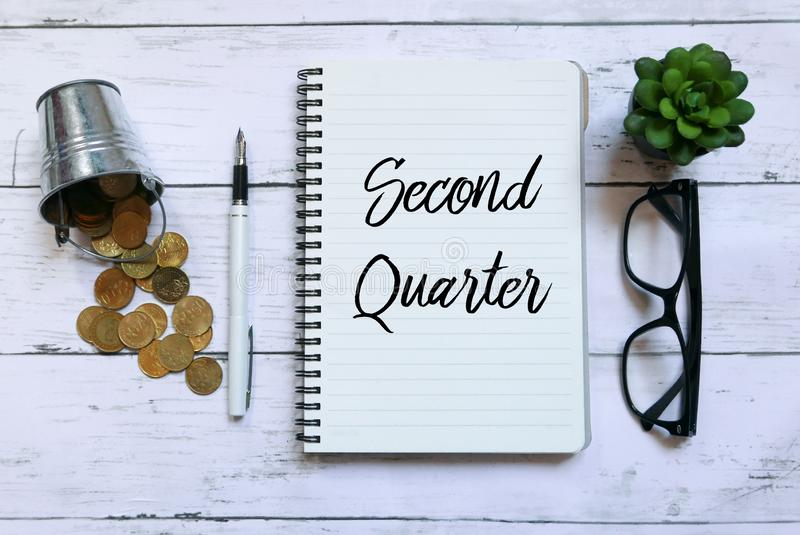 Top view of coins,glasses,plant,pen and notebook written with Second Quarter on wooden background. Business and finance concept. Top view of coins,glasses,plant royalty free stock images
