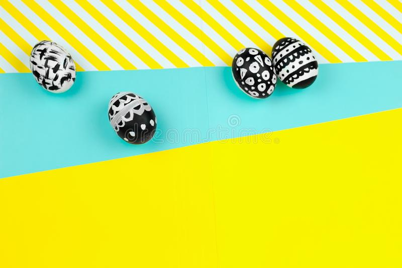 collection of dyed black and white easter eggs on a yellow and blue background royalty free stock images