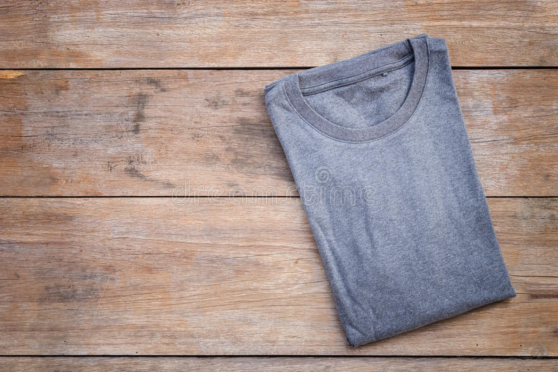 Top view of color T-Shirt on grey wood plank. Background stock photography