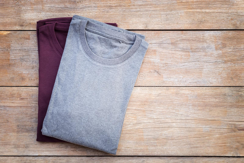 Top view of color T-Shirt on grey wood plank. Background stock photo