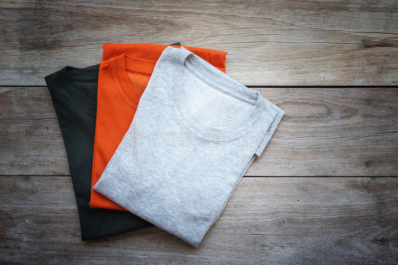 Top view of color T-Shirt on grey wood plank. Background stock images