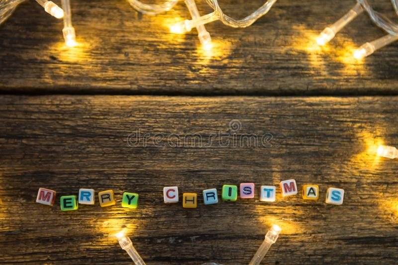 Top view of Colorful Alphabet beads. `Merry Christmas` and LED lights on wooden floor background and copy space stock image