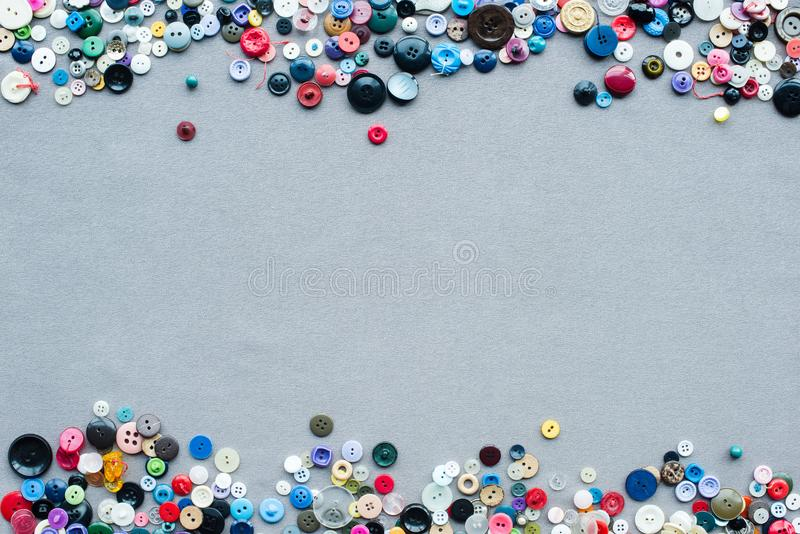 Top view of colorful buttons frame on grey. Cloth background royalty free stock photography