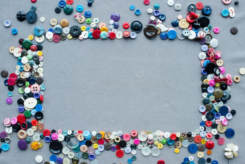 Top view of colorful buttons frame on grey. Cloth background stock photo