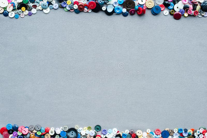 Top view of colorful buttons frame on grey. Cloth background royalty free stock image