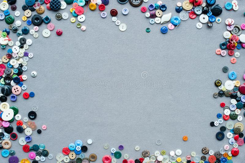 Top view of colorful buttons frame on grey. Cloth background royalty free stock images