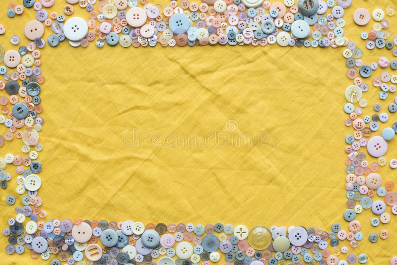 Top view of colorful buttons frame on yellow cloth background. With copy space stock photography