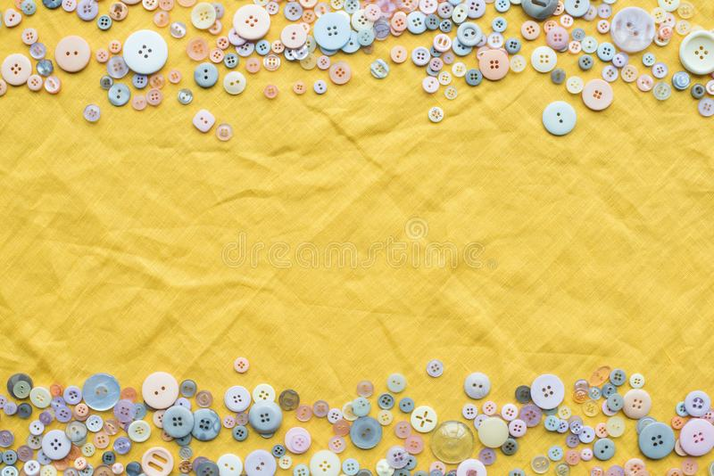 Top view of colorful buttons frame on yellow cloth background. With copy space royalty free stock photography