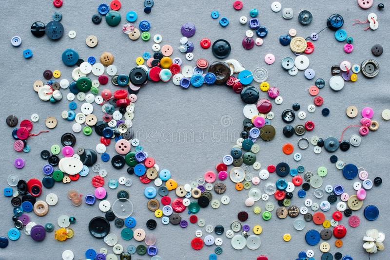 Top view of colorful buttons heart shaped frame on grey. Cloth background royalty free stock images