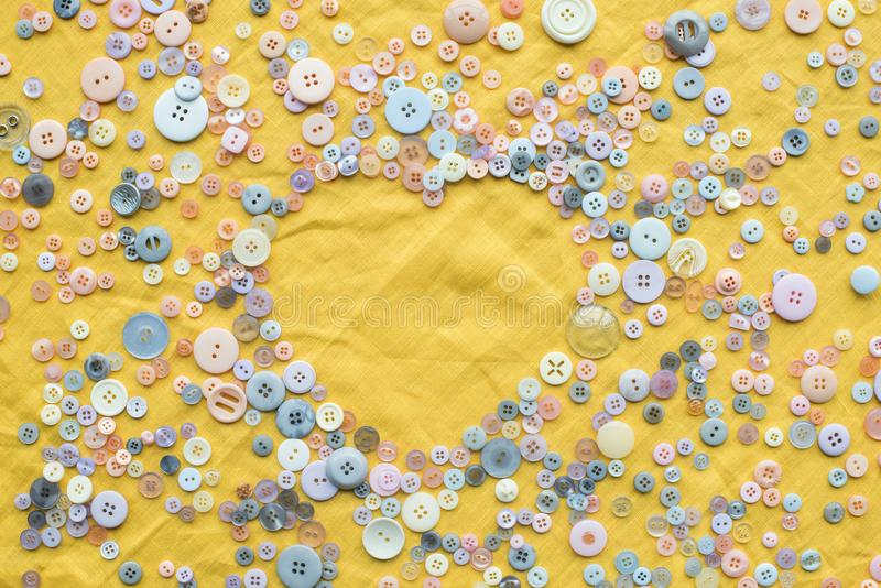Top view of colorful buttons heart shaped frame on yellow cloth background. With copy space stock photos