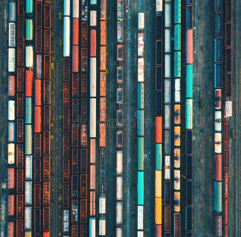 Top view of colorful cargo trains. Aerial view. From flying drone of colorful freight trains on the railway station. Wagons with goods on railroad. Heavy